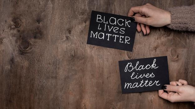 Vista dall'alto delle mani che tengono le carte di materia di vita nera con spazio di copia Foto Gratuite