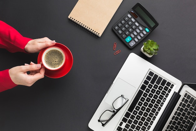 Top view of hands holding coffee cup on work desk Free Photo