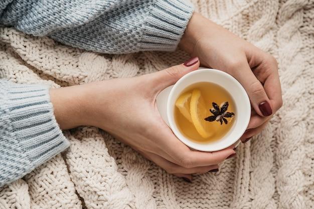 Vista dall'alto mani che tengono tazza con tè e anice stellato Foto Gratuite