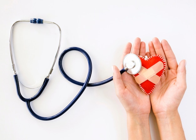 Top view of hands holding damaged heart shape with stethoscope Free Photo