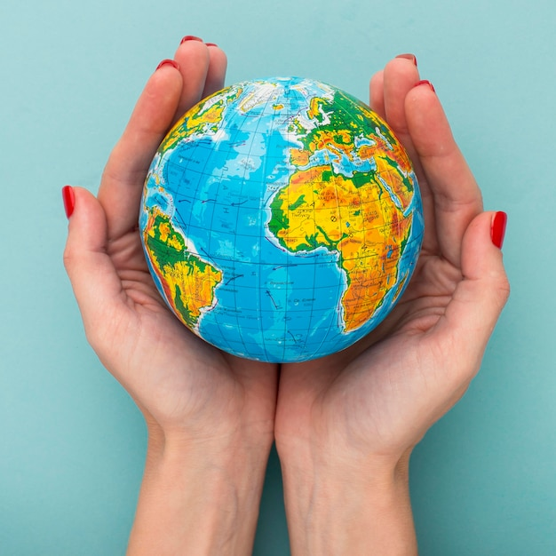 Top view of hands holding earth globe Premium Photo