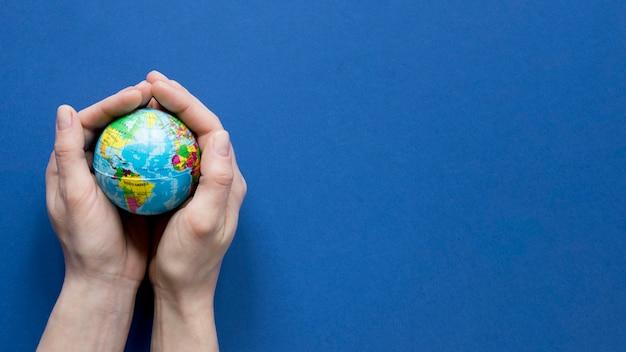 Vista superiore delle mani che tengono globo con lo spazio della copia Foto Gratuite