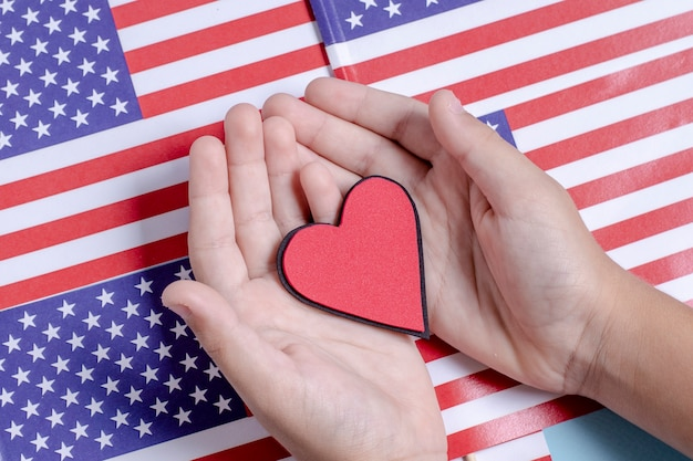 Руки взгляд сверху держа сердце на флагах сша Бесплатные Фотографии