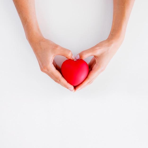 Vista dall'alto delle mani che tengono la giornata mondiale del cuore a forma di cuore Foto Gratuite