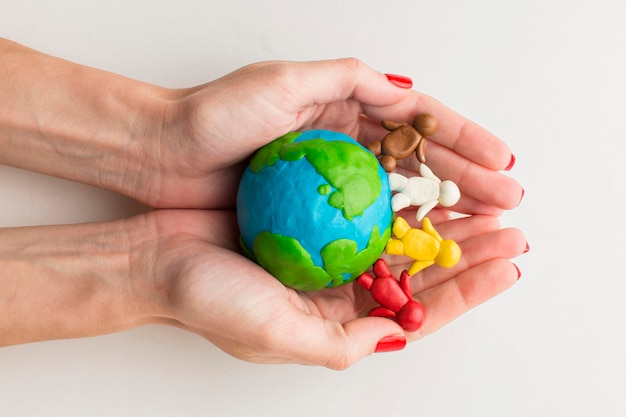 Top view of hands holding plasticine globe and people Free Photo