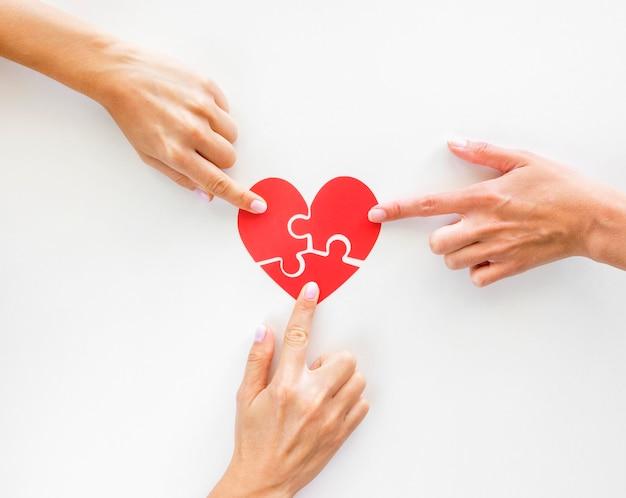 Vista dall'alto delle mani che toccano i pezzi del cuore del puzzle Foto Gratuite