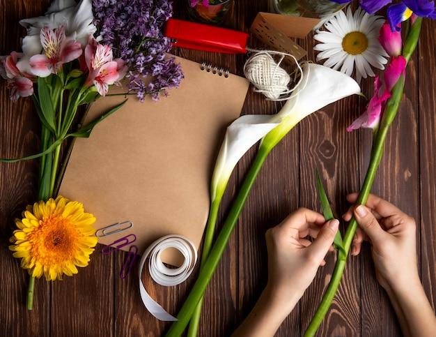 Vista dall'alto delle mani con fiori di gladiolo e rosa alstroemeria con fiori margherita lilla e uno sketchbook con pinzatrice rossa e graffette su fondo in legno Foto Gratuite