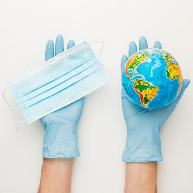 Top view of hands with gloves holding earth globe and medical mask Premium Photo