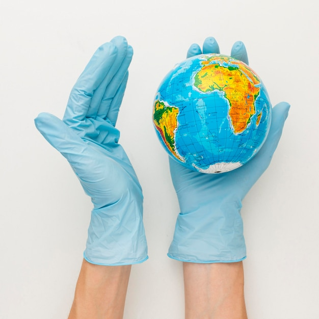 Top view of hands with gloves holding earth globe Free Photo