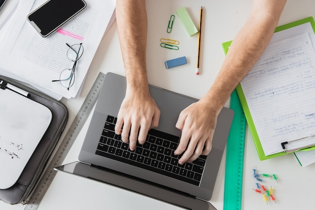 Top view hands working on laptop surrounded by stationery elements Free Photo