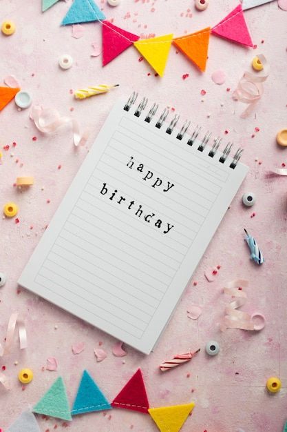 Top view of happy birthday wish on notebook with garland Free Photo