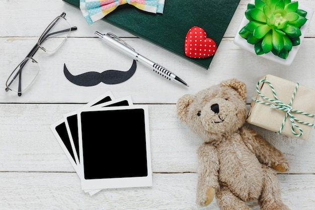 Top view Happy Father day.Blank photo for free text and accessories with tree,mustache,vintage bow tie,present,pen ,note book, and bear doll on rustic white wooden background. Free Photo