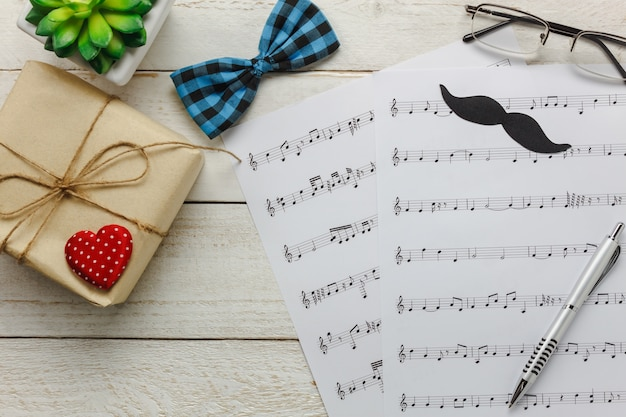 Top view happy father day with music concept.music note paper on rustic wooden background.accessories with red heart,gift,mustache,vintage bow tie,tree and present. Free Photo