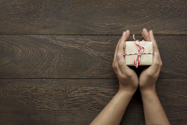 Вид сверху с новым годом фестиваля или день рождения и веселого рождества фона background.hands проведения little present.object на современном коричневом деревенском дереве на домашний офисный стол с копией пространства. Premium Фотографии