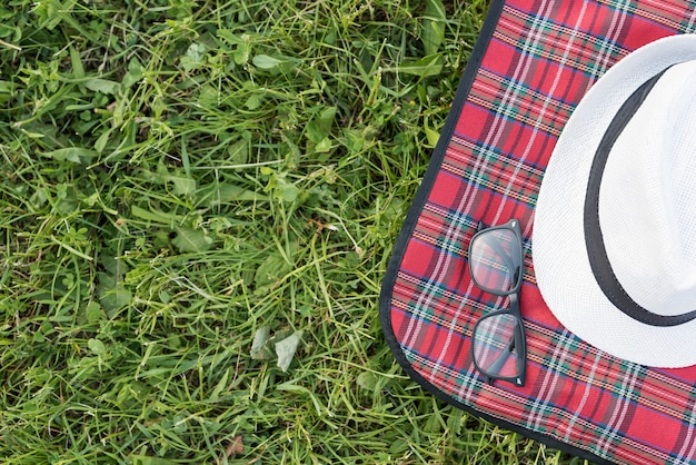 Top view hat and glasses on picnic blanket Free Photo