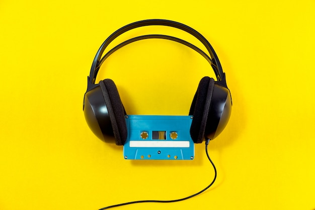 Top view of headphone and blue classic tape cassette against yellow isolated background Premium Photo
