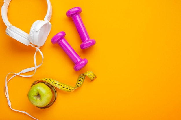Top view headphones and apple on yellow background Free Photo
