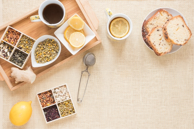 Top view of healthy breakfast with variety of herbs; lemon; strainer; bread; ginger and ingredients Free Photo