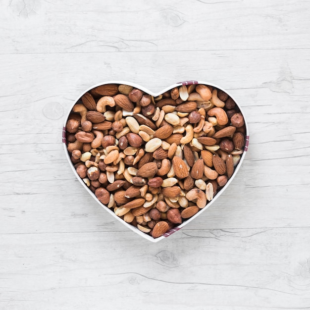 Top view of healthy dryfruits in heart shape on wooden desk Free Photo