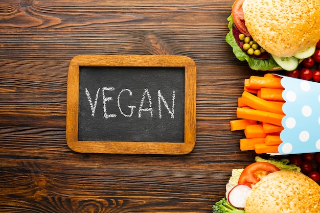 Top view healthy food arrangement with vegan lettering on chalkboard Free Photo