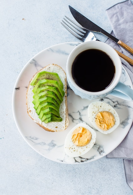 Top view of healthy vegan breakfast concept. toast with avocado and boiled eggs Premium Photo
