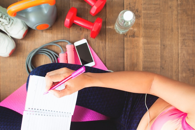 Top view healthy woman planning daily workout at home, diet and fitness concept Premium Photo