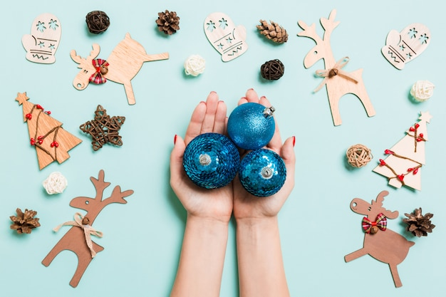 Top view of a heap of new year balls in female hands on blue backround Premium Photo