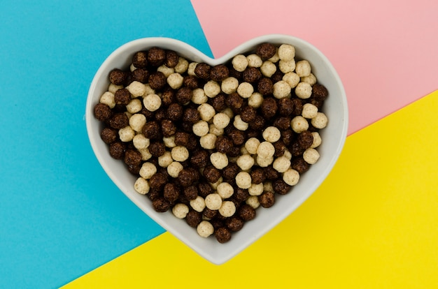 Top view heart shape bowl full with cereals Free Photo