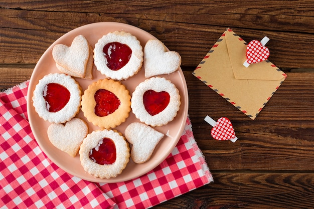 Top view of heart-shaped cookies on plate with jam Free Photo