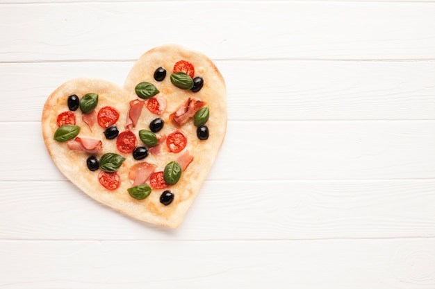 Top view heart shaped pizza on wooden table Free Photo