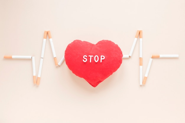 Top view heart surrounded by cigarettes Free Photo