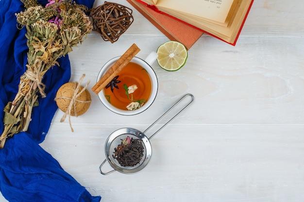 Vista dall'alto di tisane, biscotti e fiori con libri, limone, colino da tè e spezie sulla superficie bianca Foto Gratuite
