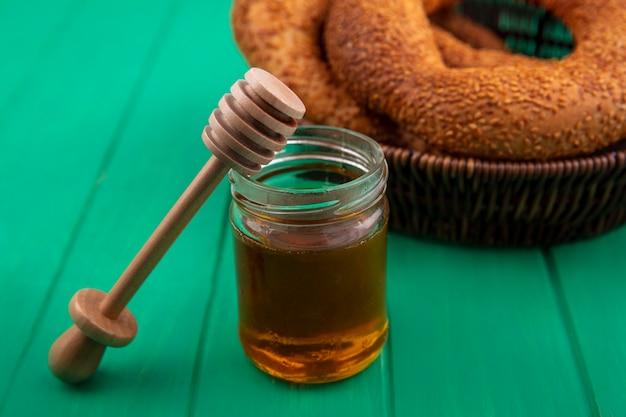 Vista dall'alto di miele su un barattolo di vetro con un cucchiaio di miele in legno con un secchio di focacce su uno sfondo di legno verde Foto Gratuite