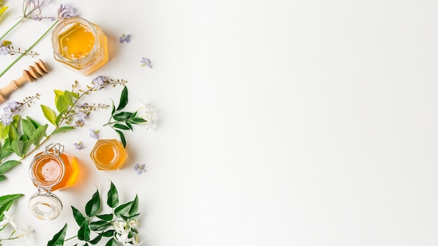 Top view honey jars with leaves Free Photo