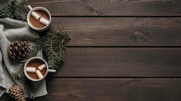 Vista dall'alto cioccolata calda con rami di pino, coni e copia-spazio Foto Gratuite