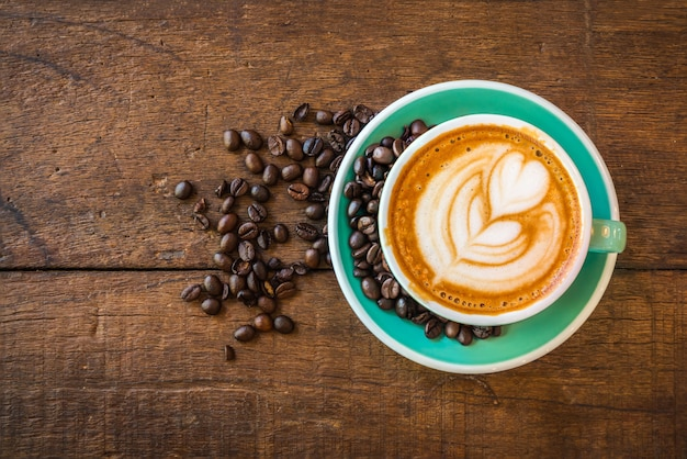 Top view of hot latte coffee with latte art and roasted coffee beans on wooden table. Premium Photo