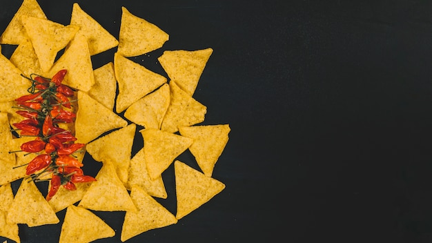 Top view of hot mexican nachos chips with red chilies over black backdrop Free Photo