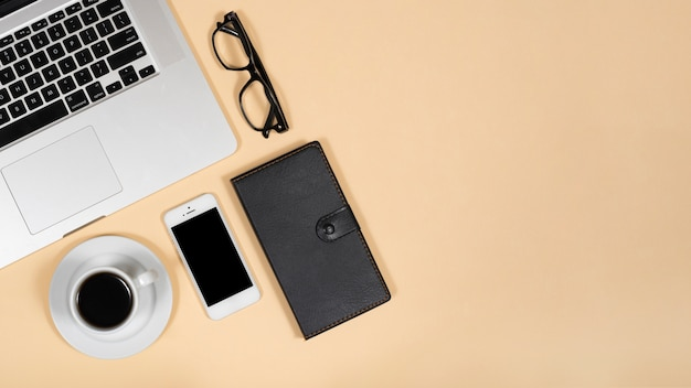 Top view of hot tea; mobile phone; eye glasses; diary and laptop over beige background Free Photo