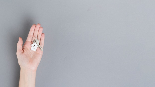 Top view of human hand holding house key over grey backdrop Free Photo
