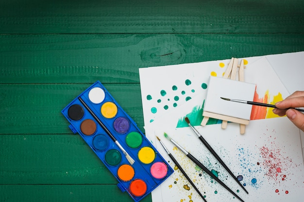 Top view of human hand holding paintbrush over painting equipment Free Photo