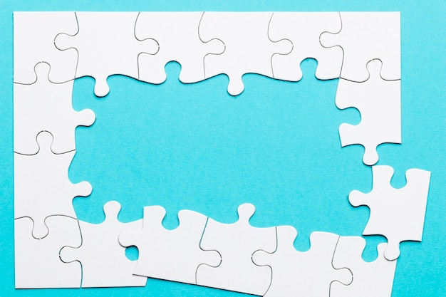 Top view of incomplete puzzle frame over blue backdrop Free Photo