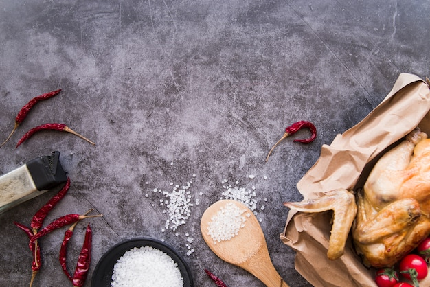 Top view of ingredients and baked chicken over concrete background Free Photo