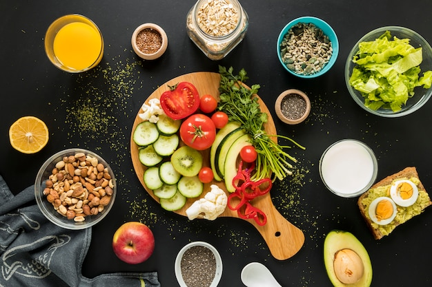 Top view of ingredients; dryfruits and vegetables on black background Free Photo