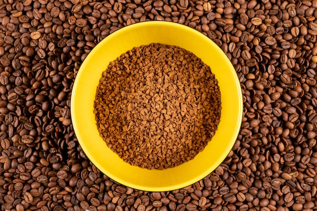 Растворимый кофе в желтой тарелке на поверхности кофейных зерен Бесплатные Фотографии