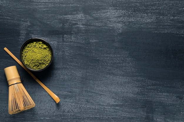 Top view isolated green tea next to traditional whisk Premium Photo