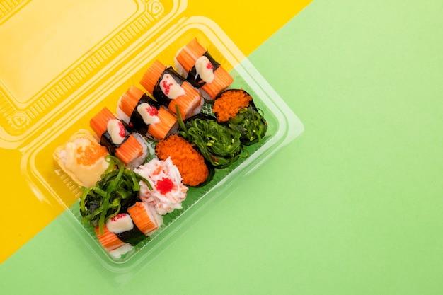 Вид сверху японской еды (суши) в прозрачной пластиковой коробке для еды Premium Фотографии