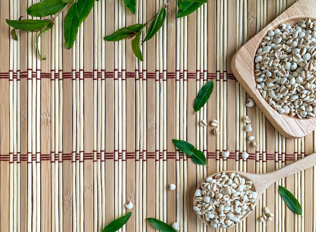 Top view of job's tears or millet on a tray and a wooden spoon. the background is a wooden mat decorated with pomegranate leaves Premium Photo