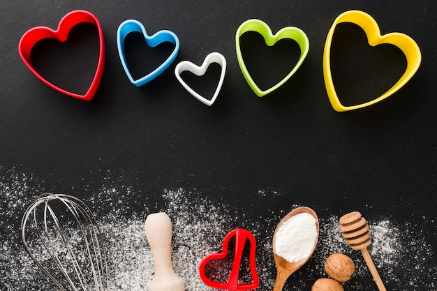Top view of kitchen utensils with colorful heart shapes and flour Free Photo