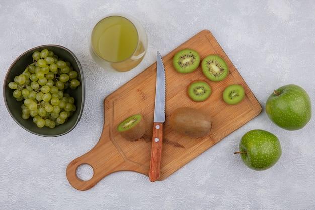 白い背景の上のガラスのリンゴジュースとボウルに青リンゴとブドウとまな板の上にナイフで上面図キウイスライス 無料写真