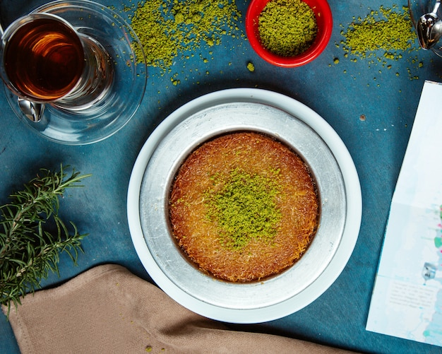 Top view of kunefe dessert garnished with pistachio served with black tea Free Photo
